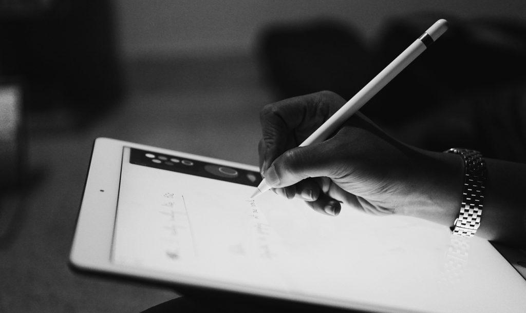 Hand met potlood op een scherm, ter verlevendiging van een een wettekst door de tekstschrijvers