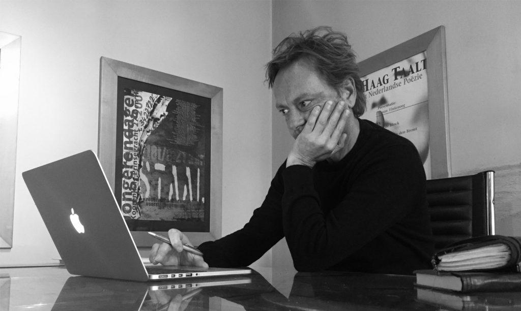 tekstschrijver Jacob achter z'n laptop met een bedenkelijke frons op het hoofd