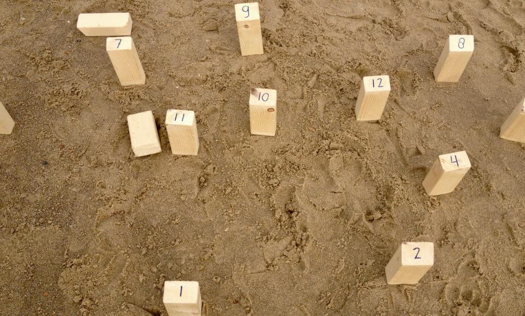 Houten plankjes met nummers op het strand, symbool voor page ranking op de SEO teksten pagina van de tekstschrijvers