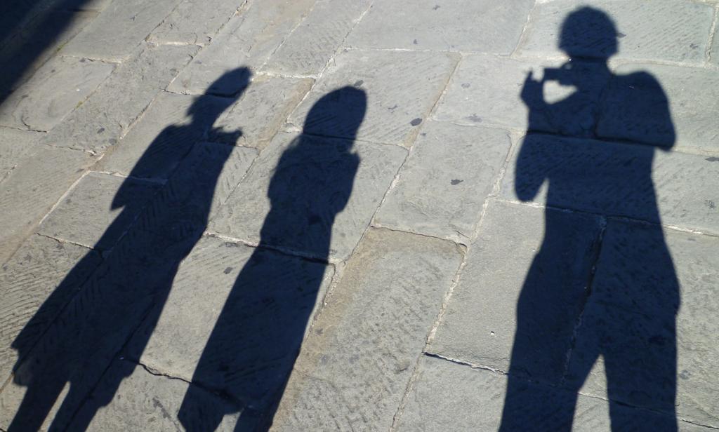 """Foto bij songtekst 'huis uit"""" silhouet van drie mensen op de straat. de tekstschrijvers"""