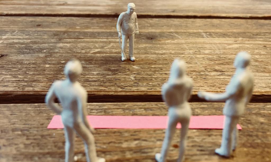 Modelpoppetjes op tafel, oud mannetje voor een kloof. Illustratie bij invloed woorden op gedrag